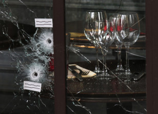 Bullet impacts are seen in the window of a restaurant window the day after a series of deadly attacks in Paris