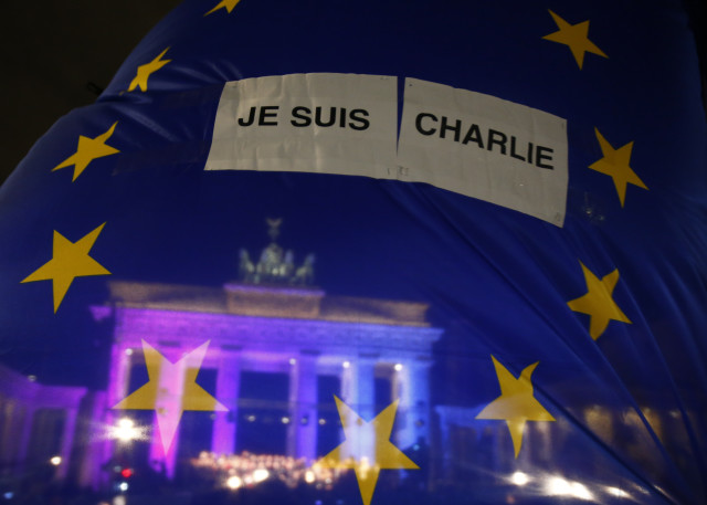 The Brandenburg Gate is seen through EU flag during a vigil  for the victims of Paris attacks in Berlin
