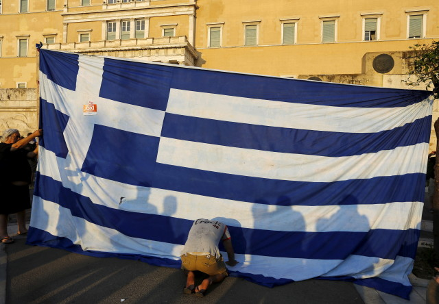 Protester kneels to pay his respect in front of a Greek flag during an anti-austerity rally in Athens