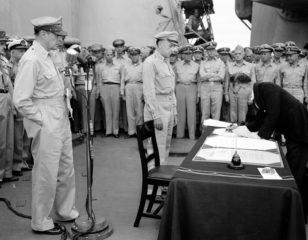 ABŞ generalı Duqlas MakArtur USS Missouri gəmisinin göyərtəsində Yaponiya xarici işlər naziri Manoru Şigemitsunun təslim aktı imzalamasını seyr edir.