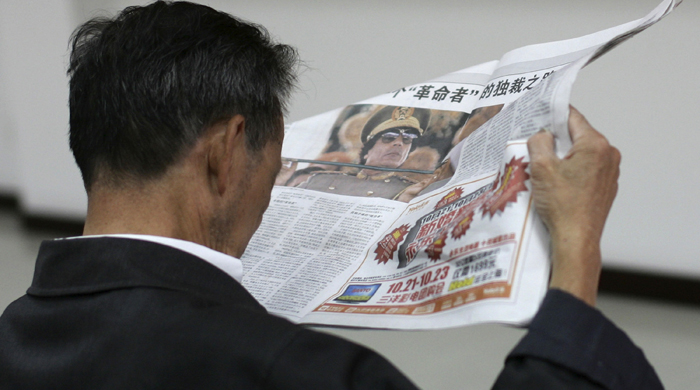 A man reads a local newspaper's story on the spread pages featuring a photo of Moammar Gadhafi