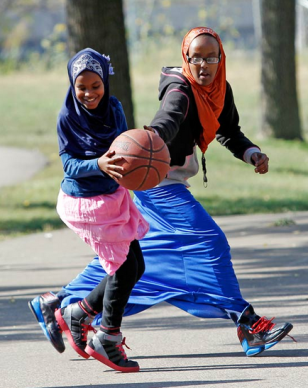 While many Somalis have adapted slowly to American life, a sense of alienation persists for some, giving an opening for recruiters from Al-Shabab and Islamic State. In this September 27, 2013, file photo, young women play basketball before the start of a rally by the Minneapolis Somali community against terrorism. (Reuters)