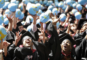 Students throw inflatable globes into the air as they celebrate graduation during Harvard University commencement exercises. (AP Photo)