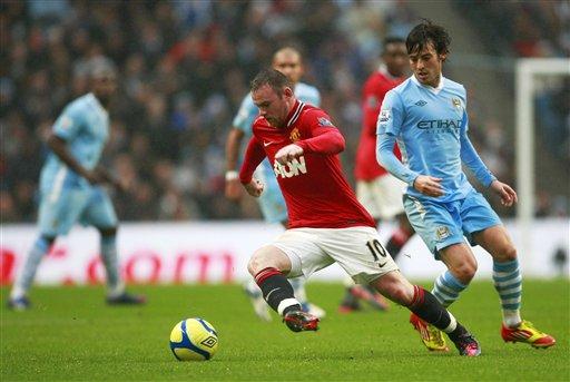 David Silva na Manchester City (dama) yana kokarin kwace kwallo daga kafar Wayne Rooney na Manchester United a karawar da suka yi na gasar cin Kofin FA a filin wasan Etihad dake birnin Manchester, Ingila, ran Lahadi 8 Janairu 2012.