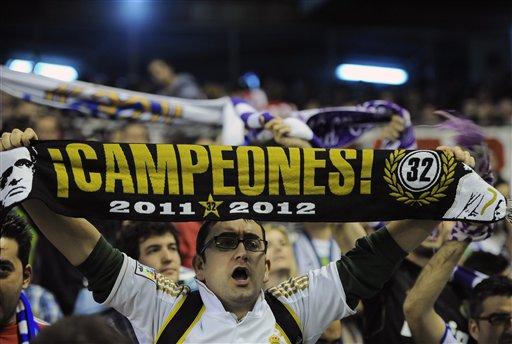 """Wani mai goyon bayan kungiyar Real Madrid dauke da kyalle mai cewa """"Zakarun 2011-2012"""" a bayan da kungiyarsa ta zamo zakarar rukunin lig-lig na kasar Spain, La Liga, bayan ta doke Athletic Bilbao a filin wasa na San Mames dake Bilbao, laraba 2 Mayu 2012."""