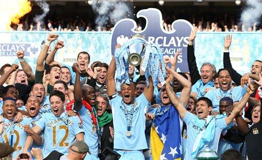 'Yan wasan Manchester City su na murna dauke da kofin zakarun wasannin lig-lig na kasar Ingila, bayan da suka doke Queens Park Rangers, yau lahadi 13 Mayu 2012.