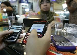 Penjual BlackBerry di sebuah pusat perbelanjaan di Jakarta sedang memeriksa barang dagangannya (foto: AP).