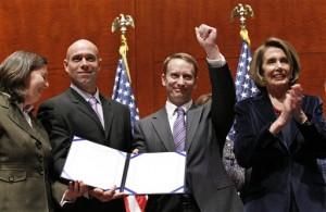 Ketua DPR Nancy Pelosi (kanan) bertepuk tangan sementara dua anggota militer Stacy Vasquez (kiri) dan Letkol Victor Fehrenbach, dan Mayor Mike Almy, memegang UU yang telah ditandatangani untuk mencabut kebijakan 'Don't Ask Don't Tell' di Kongres AS, Selasa, 21 Desember 2010 (AP Photo/Alex Brandon).