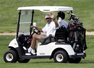 Presiden Obama melambaikan tangan dari atas kereta golf.
