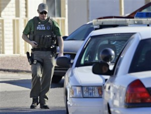 Seorang polisi berjalan di depan rumah Jared Lee Loughner di Tucson, Arizona, Sabtu, 8 Januari 2011 (AP Photo/Matt York).