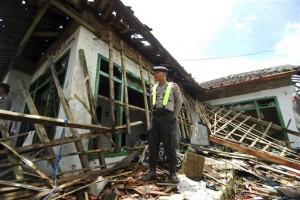 Seorang polisi berdiri di atas puing-puing rumah anggota Ahmadiyah yang diserang massa di Cikeusik, Senin (2/7).