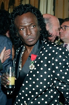 Miles Davis holds a glass of orange juice after receiving the Chevalier de la Legion d'Honneur award medal in Paris from the French government, July 16, 1991
