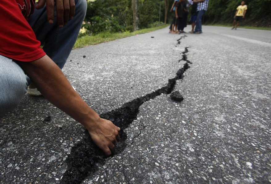 An Indian boy shows a crack of damaged road in Gangtok, India. (AP)