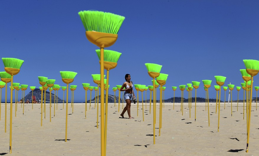 A woman walks near brooms placed at Copacabana beach as a form of protest in Rio de Janeiro. (Reuters)