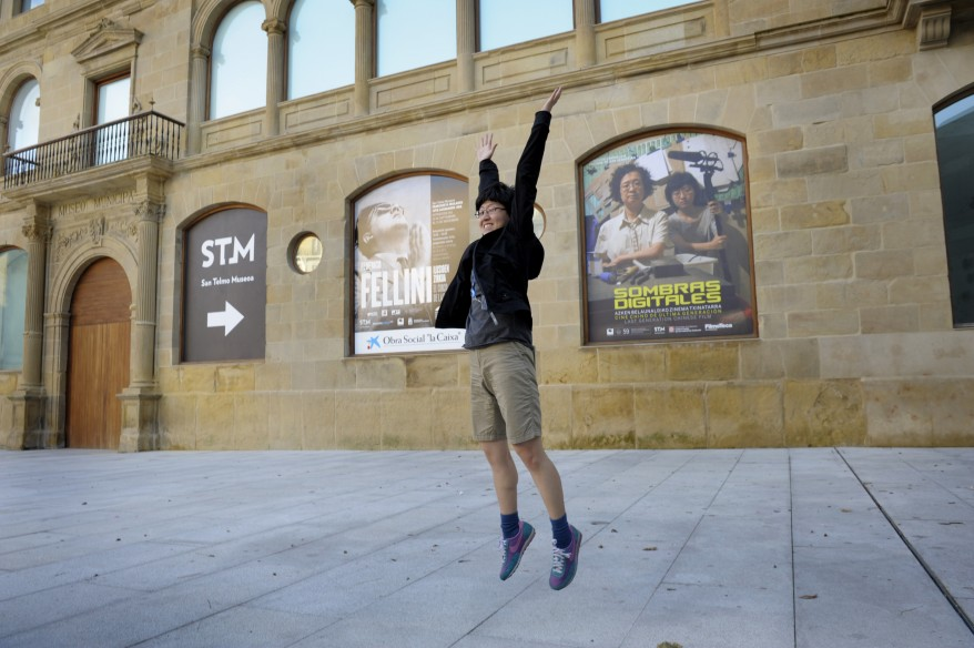 "Chinese director Liu leaps in front of a poster for ""Digital Shadows: Last Generation Chinese Film"" at the San Sebastian Film Festival. (Reuters)"