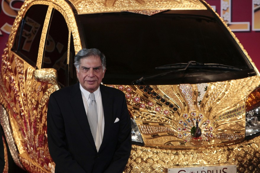 Chairman of Tata Group Ratan Tata poses in front of a Nano car made of gold during a ceremony in Mumbai (Reuters)