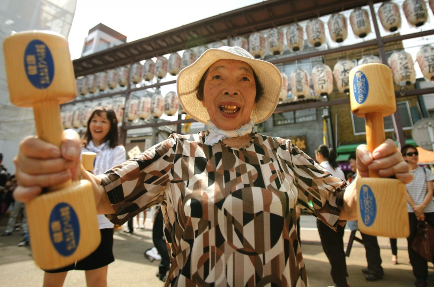 "Woman exercises with wooden dumbbells during a health promotion event to mark Japan's ""Respect for the Aged Day"" at a temple in Tokyo. (Reuters)"