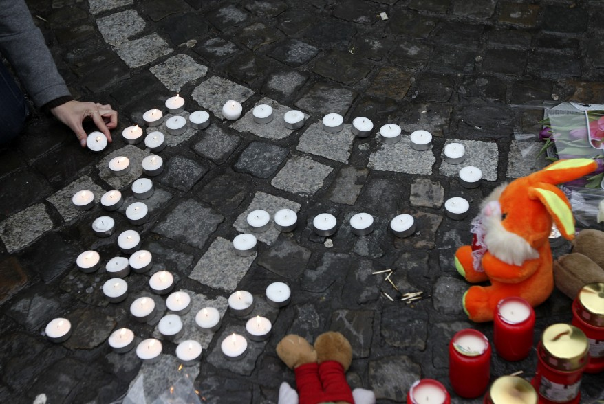 A woman lights a candle at a bus stop where a grenade-lobbing gunman killed three people and injured 123, in the city center of Liege, Belgium. (AP)