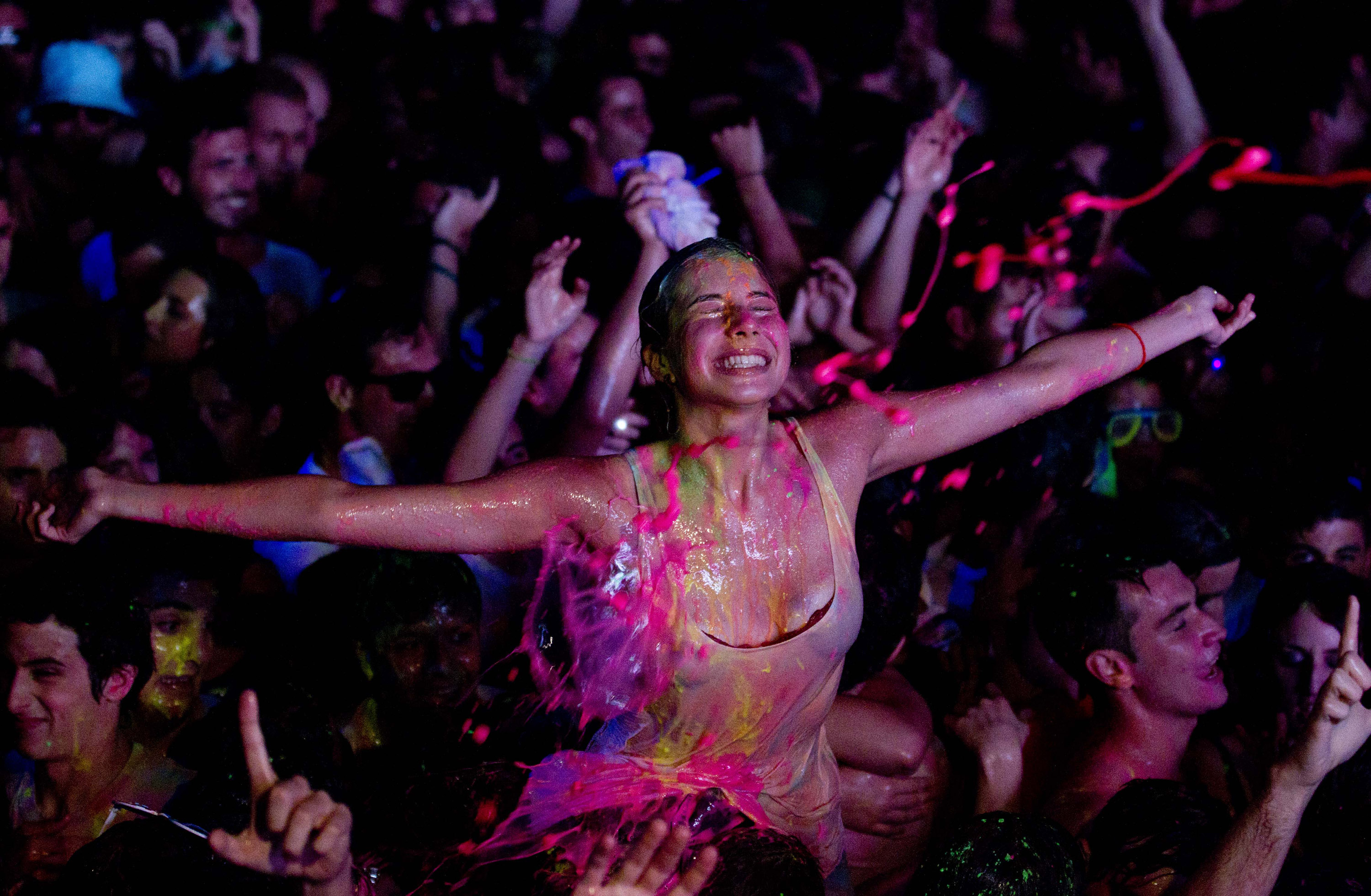 a reveler reacts during a glow paint party in the early