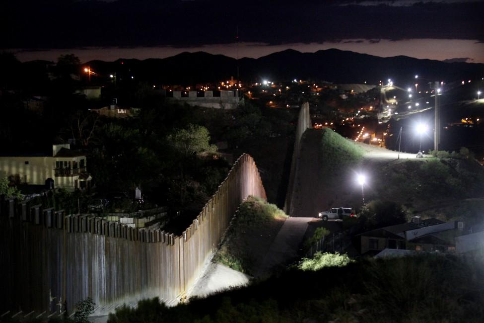 The US/Mexico border wall is illuminated at night July 6, 2012 in Nogales, Arizona.