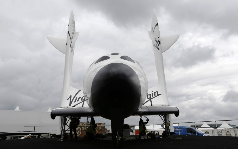 Workers prepare Virgin Galactic's SpaceShipTwo ahead of the Farnborough Airshow 2012 in southern England, July 7, 2012. (Reuters)