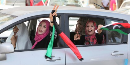 Libyan women celebrate the holding of elections by waving a Libyan flag and flashing the victory sign as they drive in Tripoli, Libya, July 7, 2012. (AP)