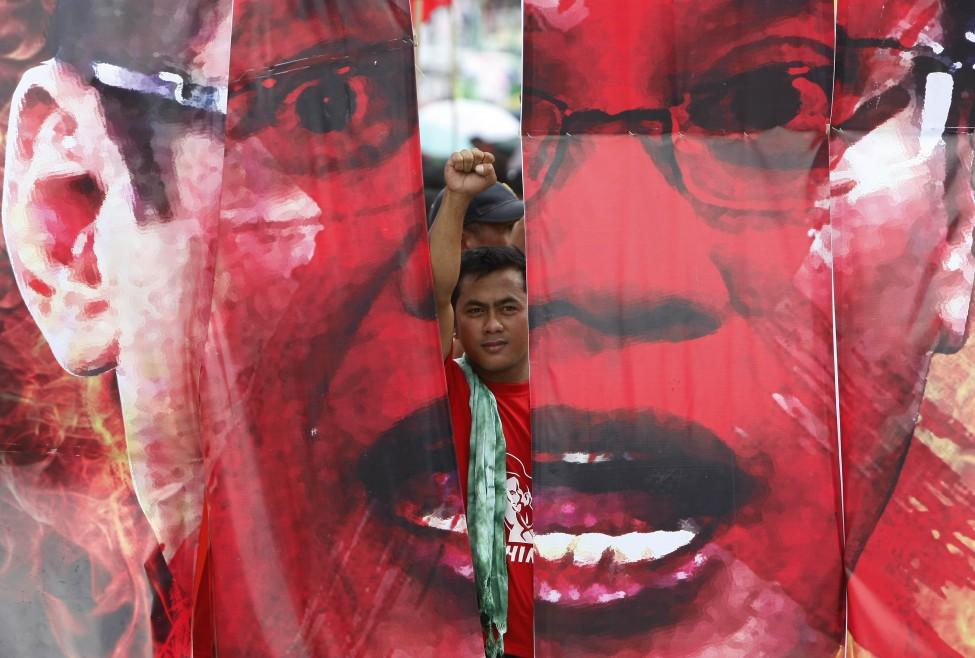 示威者在菲律宾总统阿基诺三世肖像后挥拳抗议他的国情咨文演说