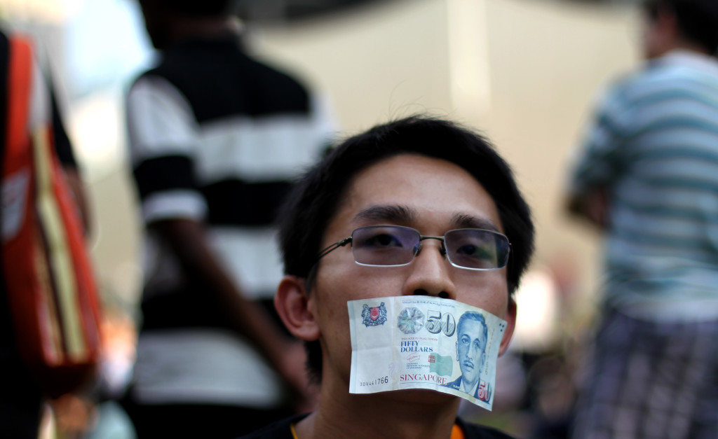 A man covers his mouth with a fifty dollar bill represent the lost of free speech at the Speakers Corner on Saturday, June 8, 2013 in Singapore to protest a new government policy requiring news websites to obtain licenses.