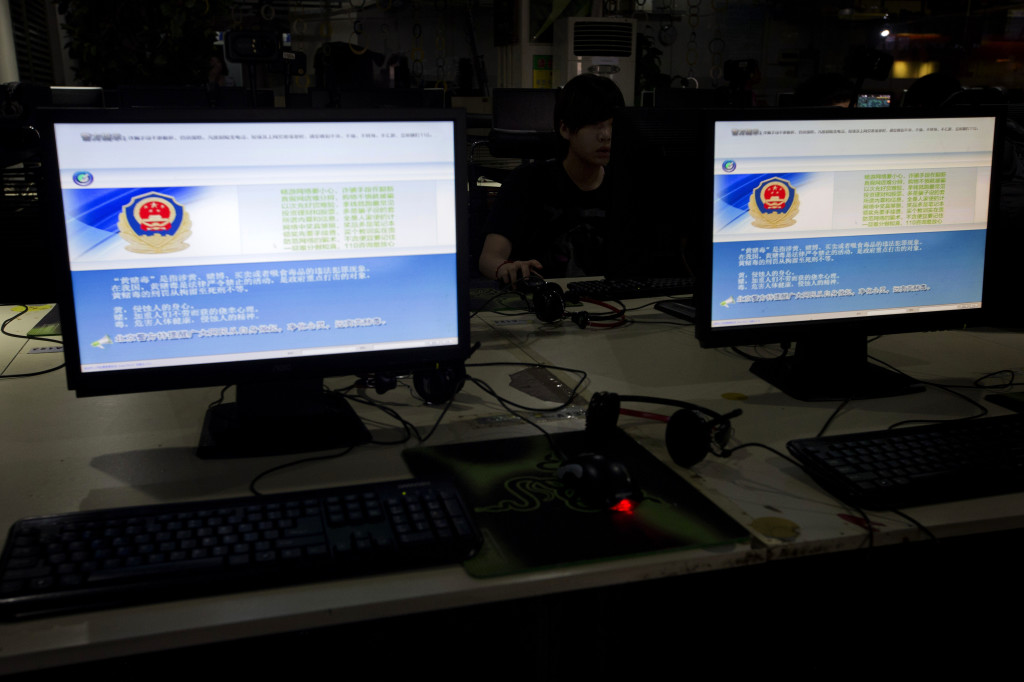 A computer user sits near displays with a message from the Chinese police on the proper use of the internet at an internet cafe in Beijing, China, Monday, Aug. 19, 2013.