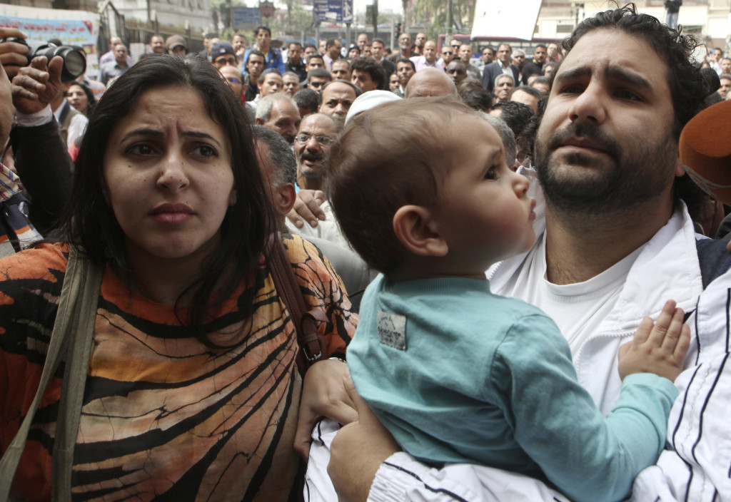 Alaa Abdel Fattah (R), one of the activists who was summoned by the public prosecutor on whether he had a role in the recent violent anti-Islamists protests, arrives with his wife and child to the public prosecutor's office in Cairo, March 26, 2013. Fattah was arrested November 28 on charges he violated Egypt's new anti-protest laws. REUTERS/Asmaa Waguih