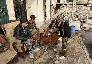 In one of the last photos taken by freelance photographer Molhem Barakat, Hasan, an 11 year-old fighter from the Free Syrian Army distributes tea to his fellow fighters in Aleppo's Karm al-Jabal district December 7, 2013.  Barakat was only a few years older than the boys pictured. REUTERS/Molhem Barakat