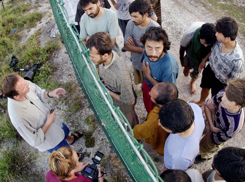 Refugees gather on one side of a fence to talk with international journalists about their journey that brought them to the Island of Nauru, Wednesday, Sept. 19, 2001. The refugees were part of 517 rescued from sinking boats north of Australia and will be detained until their claims for asylum can be processed. (AP Photo/Rick Rycroft)
