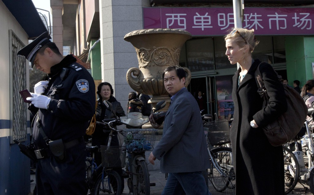 A Chinese police man checks the identity of a foreign journalist near the Xidan shopping district, one of two sites designated on an internet call for protest in Beijing, China, Sunday, March 6, 2011. The Chinese capital began ramping up controls on foreign journalists amid calls on the Internet for anti-government protests styled on those rocking the Middle East and North Africa.