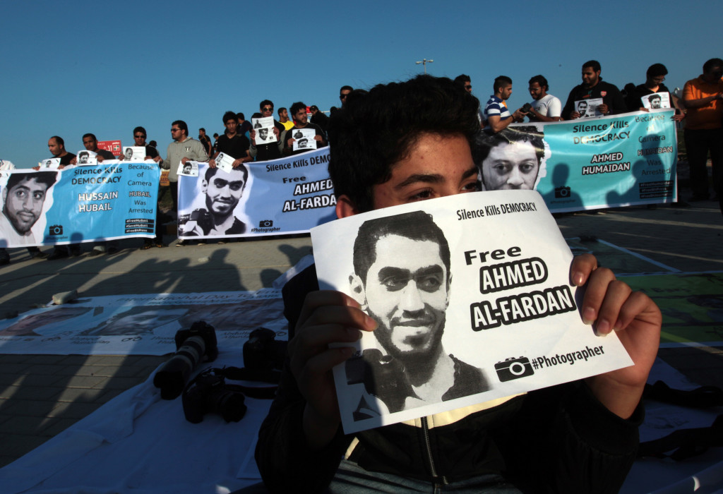 "Bahraini anti-government protesters carry signs with images of jailed photographers, demanding their freedom, during a march Friday, Jan 3, 2014, in the northern village of Barbar, Bahrain. Thousands shouted ""down with the government"" during the march called by several opposition societies seeking democracy in the Gulf island kingdom. (AP Photo/Hasan Jamali)"
