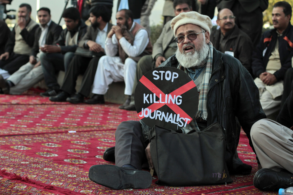 A journalist holds a placard while taking part in a demonstration in front of the Parliament building in Islamabad January 28, 2013. Journalists from all over the country held a demonstration on Monday against a recent spate of killings of journalists and demand compensation for the deceased. REUTERS/Faisal Mahmood