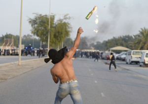 An anti-government protester throws a Molotov cocktail at riot police during clashes after the funeral procession of Ahmed Abdul-Ameer in the village of Sanabis, west of Manama, November 30, 2013.  According to police, Abdul-Ameer died after suffering burns as he tried to set a warehouse on fire during an anti-government protest. Opposition activists said that he died when he tried to burn tires on the road to create road blocks in the village. REUTERS/Stringer