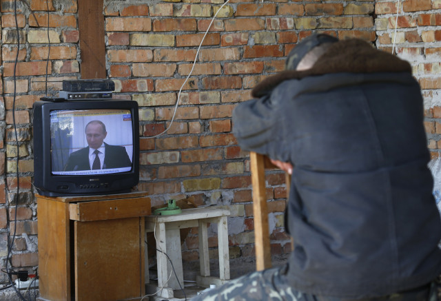 A Ukrainian serviceman watches a TV broadcast of Russian President Vladimir Putin signing a law on ratification of a treaty making Crimea part of Russia, at a Ukrainian military base in the Crimean town of Belbek March 21, 2014. Russia's upper house of parliament unanimously approved a treaty on annexing Ukraine's Crimea region on Friday, clearing the way for President Vladimir Putin to sign it into law. REUTERS/Vasily Fedosenko