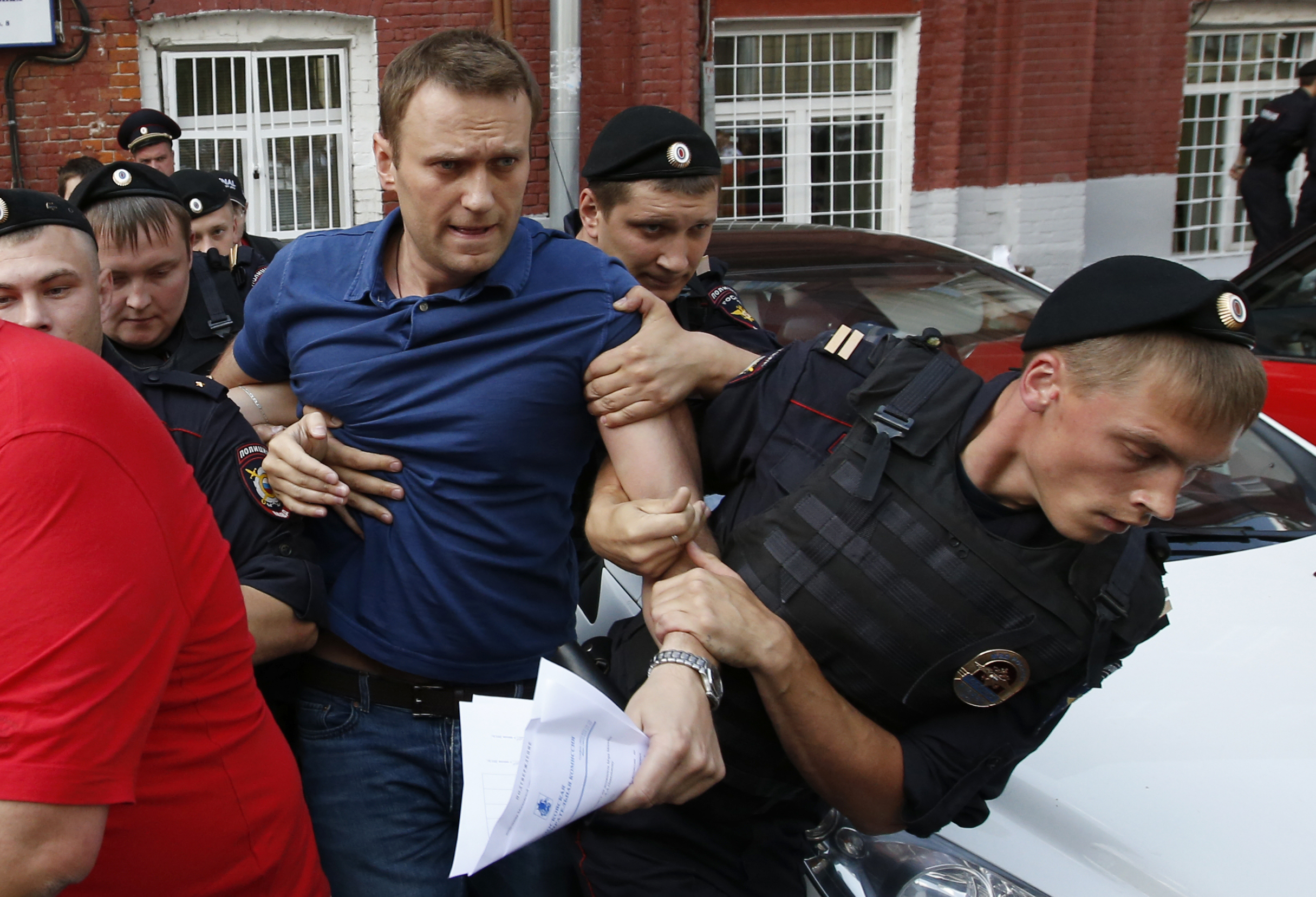 "Policemen detain Russian opposition leader and anti-corruption blogger Alexei Navalny (C), after he visited the city's election commission office to submit documents to get registered as a mayoral election candidate, in Moscow July 10, 2013. Protest leader Alexei Navalny vowed he would destroy the political system under President Vladimir Putin that was ""sucking the blood out of Russia"", after state prosecutors demanded he be jailed for six years on theft charges. Other opposition figures say the trial was intended to prevent Navalny from fulfilling his dream of becoming president and, before that, running for Moscow mayor in September. Navalny was detained on a charge of organizing an unsanctioned rally near the city's election commission office and was then released in less than half an hour. REUTERS/Grigory Dukor"