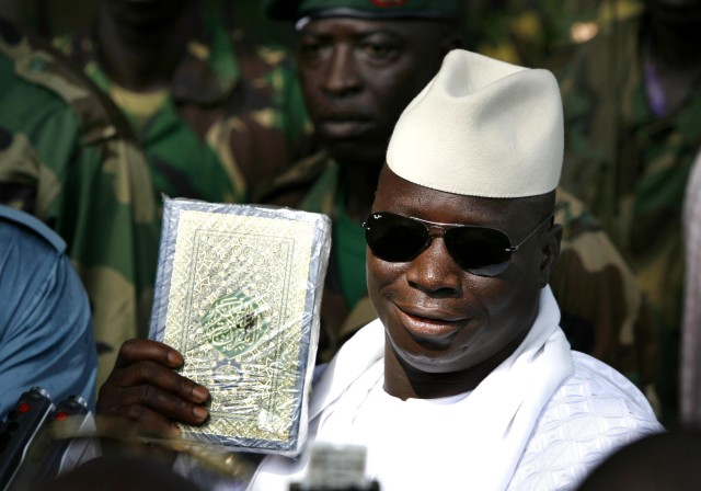 Gambian President Yahya Jammeh holds up a Koran while speaking to the media  after casting his ballot in the presidential elections in Banjul September 22, 2006. REUTERS/Finbarr O'Reilly