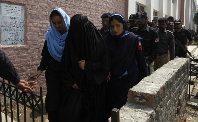 Police escort Salma alias Fatima (dressed in black), 40, who was arrested under the blasphemy law, as she leaves after appearing in the district court in Lahore September 17, 2013. Upon the allegations of the Imam of a local mosque, police filed a case against the school principal under the blasphemy law on September 2, 2013. The accused, who runs a secondary school, has denied the charges and claims that the complainant had a personal grudge against her, local media reported. REUTERS/Mohsin Raza