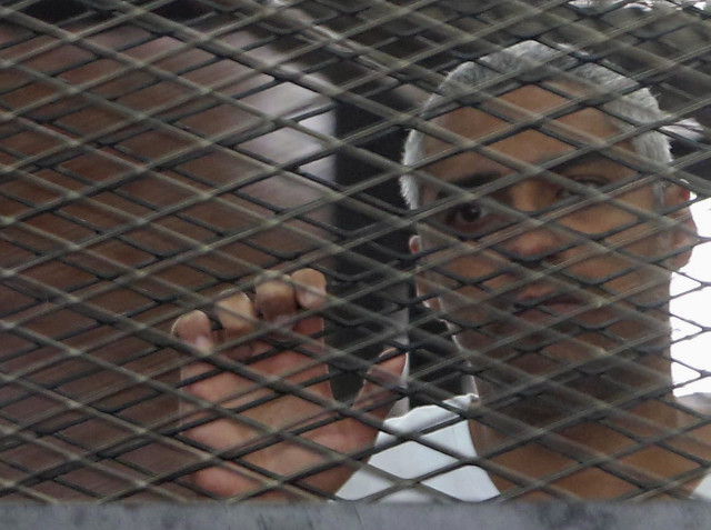 Al Jazeera journalist Mohammed Fahmy stands behind bars at a court in Cairo May 15, 2014. REUTERS/Stringer