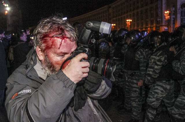 Wounded Reuters photographer Gleb Garanich, who was injured by riot police, takes pictures as riot police block protesters during a scuffle at a demonstration in support of EU integration at Independence Square in Kiev November 30, 2013. The International News Safety Institute says 58 journalists or media staff have been killed while working in 2014 alone. REUTERS