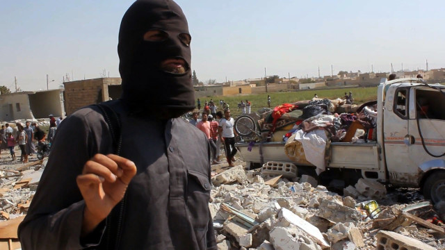 An image grab taken from an AFPTV video on September 16, 2014 shows a jihadist from the Islamic State (IS) group standing on the rubble of houses after a Syrian warplane was reportedly shot down by IS militants over the Syrian town of Raqa. The plane crashed into a house in the Euphrates Valley city, the sole provincial capital entirely out of Syrian government control, causing deaths and injuries on the ground. AFP PHOTO / AFPTV / STR