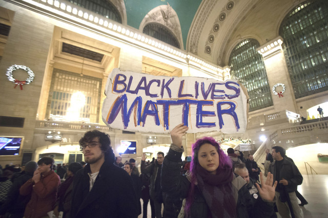 Demonstrators protest to demand justice for the death of Eric Garner, at Grand Central Terminal in the Manhattan borough of New York, December 9, 2014. The death in New York of Garner, a 43-year-old father of six, and the police shooting in Ferguson, Missouri, of Michael Brown, have highlighted strained relations between police and black Americans and rekindled a national debate over race relations.    REUTERS/Carlo Allegri