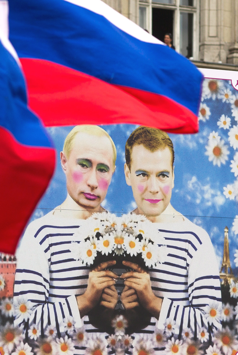 russian rights activists fly national flag next to poster with
