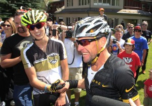 Lance Armstrong, front, talks to reporters after his second-place finish in the Power of Four mountain bicycle race at the base of Aspen Mountain in Aspen, Colo., on Aug. 2. Race-winner Keegan Swirbul, 16, of Aspen, left, claps his hand. The race was the first public appearance for Armstrong since the U.S. Anti-Doping Association banned him for life from professional cycling. Photo: AP/David Zalubowski