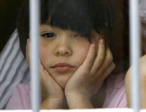 An orphan child looks out from a window at an orphanage in the southern Russian city of Rostov-on-Don