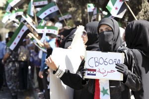 "Syrian woman holding ""Freedom"" poster protests against Russia's support for Syrian President Bashar al-Assad. Photo: Reuter"
