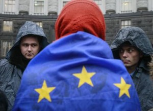 A protester wrapped in a European Union flag confronts two riot policemen guarding Ukrainian cabinet of ministers building in Kyiv on Monday, the fourth day of protests. Photo: Reuters: Gleb Garanich