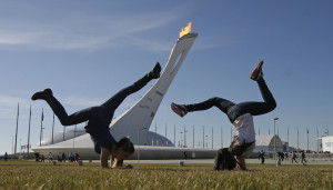Winter Olympics? Girls in Sochi practice cartwheels on grass in front of the Olympic Flame on Feb. 12. Photo: AP/Darron Cummings